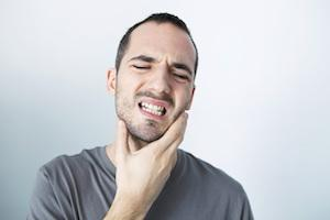 Man holding jaw from tooth pain | Dentist Calgary AB