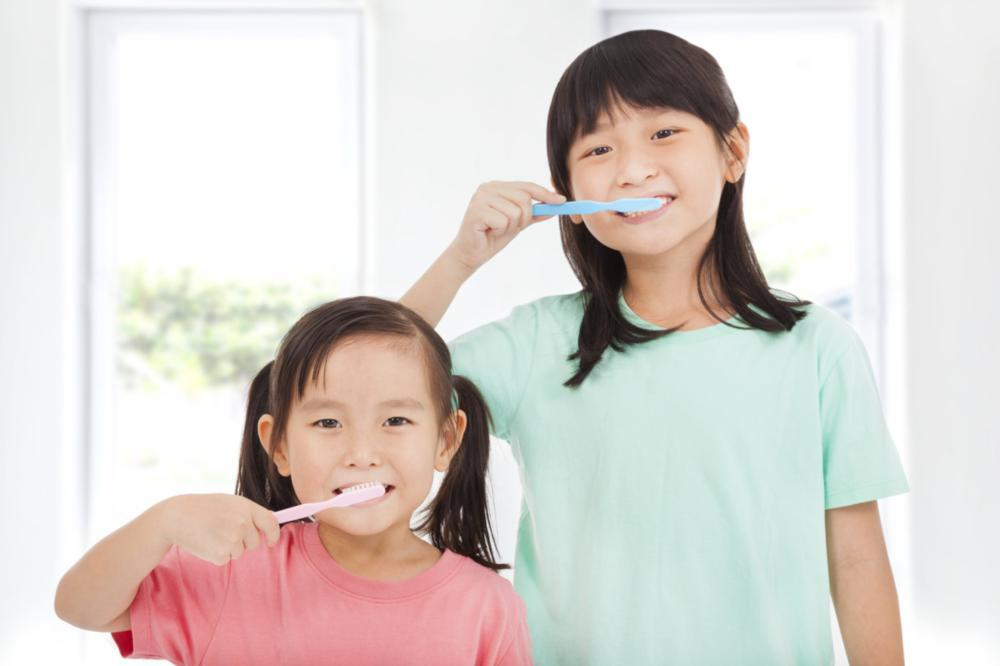 Two young girls brushing their teeth | Dentist Calgary AB