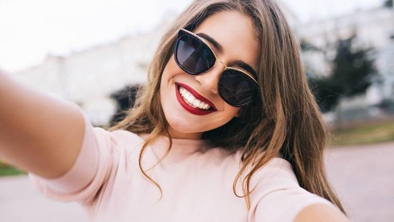 woman in red lipstick taking a selfie wearing sunglasses